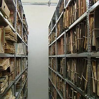 Mappeja ja asiakirjoja hyllyissä.