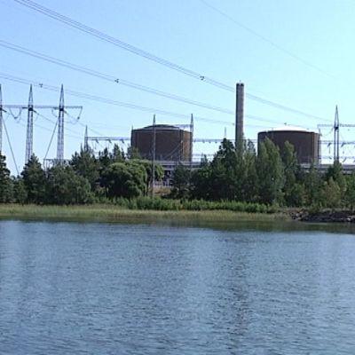 Loviiisan ydinvoimalan reaktorit ja siirtoverkon sähköpylväitä.