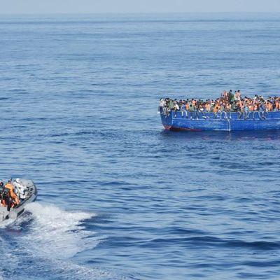 Puinen kalastusalus täynnä ihmisiä Välimerellä.