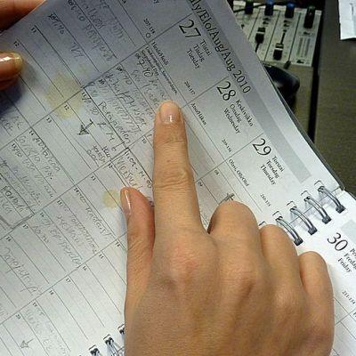 Nainen selailee kalenteriaan työpöydän ääressä.