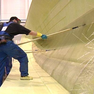 Kuvassa veneenrakentajat muokkaavat lasikuituveneen pohjaa.