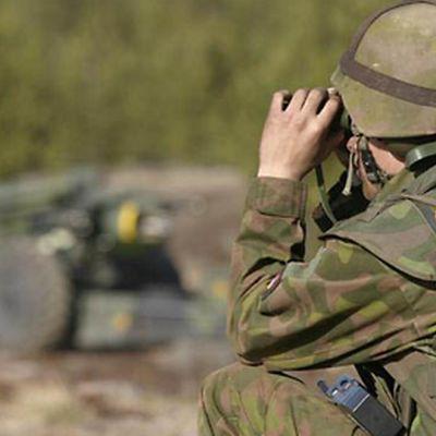 Suomalaisen armeijan varusmies rynnäkkökivääri olallaan.