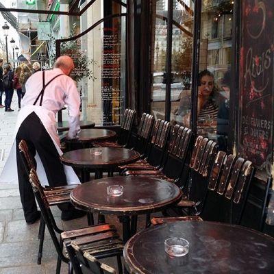 Tarjoilija pyyhkii pöytiä