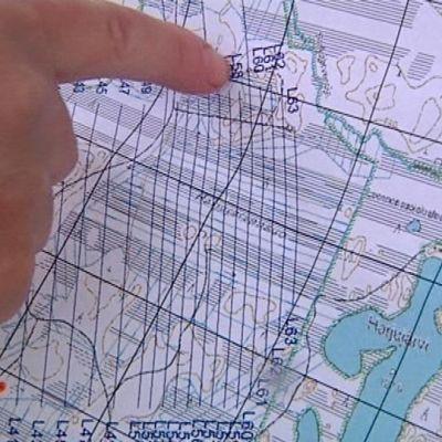 Tutkija näyttää sormella kartalta tutkimusaluetta.