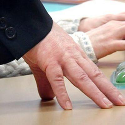 Työntekijöiden kädet toimiston pöydällä.