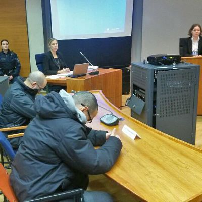Kaksi syytettyä ja oikeuden henkilökuntaa oikeussalissa