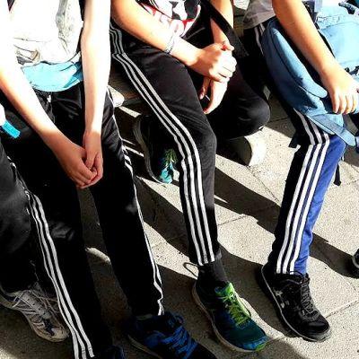 Alakouluikäiset lapset istuvat vierekkäin penkillä, yhdellä on reppu sylissään.