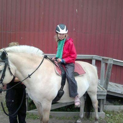 Tyttö hevosen selässä.