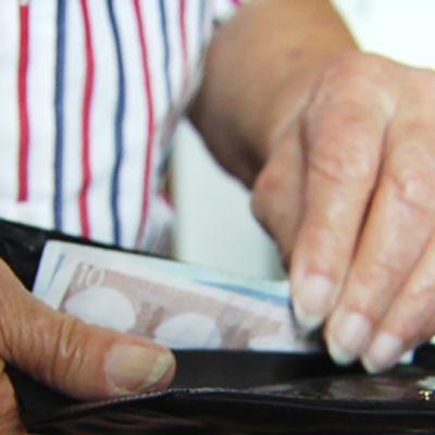 Vanhempi ihminen ottaa rahaa lompakosta.