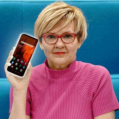 Kuvassa Virpi Hukkanen ja vilkkuva älypuhelin.