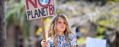 """Liten flicka på en mans axlar håller i en skylt med texten """"There is NO planet B""""."""