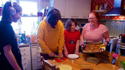 En mor och tre barn lagar mat tillsammans.