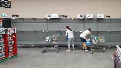 Kaksi naista ottaa viimeiset vessapaperipaketit kaupan hyllyltä Gold Coastin kaupungissa Australiassa.