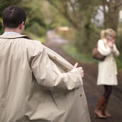 En man öppnar sin jacka framför en kvinna på en skogsväg.