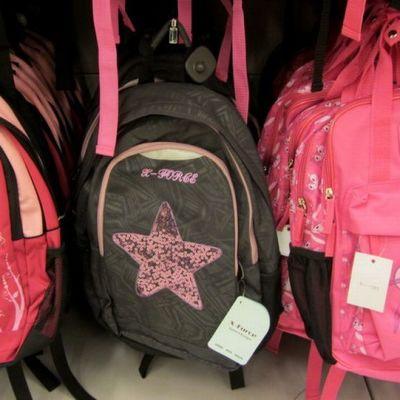 Pinkkejä ja punaisia koulureppuja rivissä.