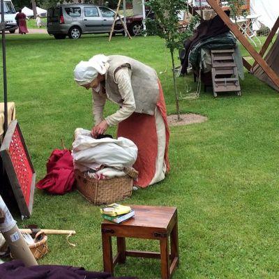 Kuvassa keskiaikaiseen asuun pukeutunut nainen kumartuu ottamaan jotakin valkeasta säkistä. Nainen seisoo nurmella ja kuvassa näkyy myös kaksi telttaa.