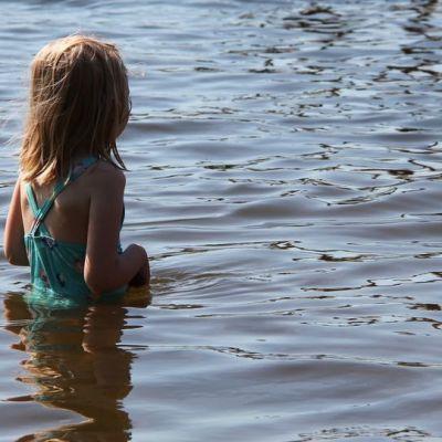 Lapsi hytisee järvivedessä.