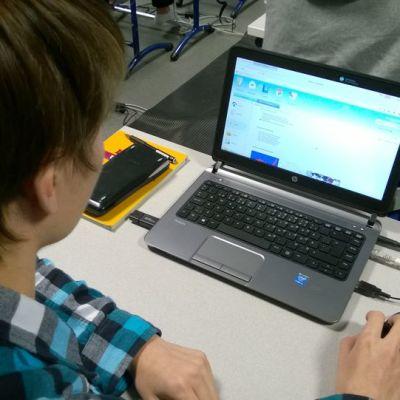 Lukiolainen tekee kemian koetta tietokoneella Espoonlahden lukiossa.