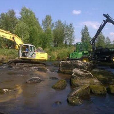 Keltainen kaivuri ja vihreä metsötraktori kosken vedessä.