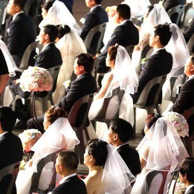 Tuoliriveittäin valkoisiin hääpukuihin ja huntuihin pukeutuneita morsiamia sekä sulhasia mustissa puvuissa.