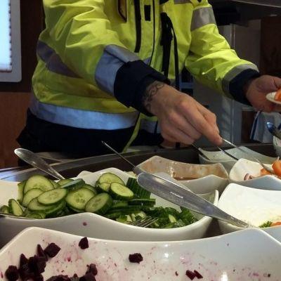 Mies ottaa salaattia lautaselle