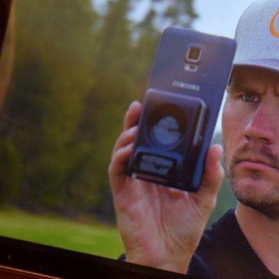 Mies käyttää kännykällään Caddieye-väylämittaria mainosvideolla