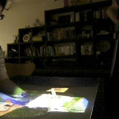 Aasialainen mies ohjaa käsillään kuvia vesiastiassa.