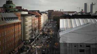 en stadsbild ovanifrån en gata i helsingfors men olika höghus till vänster om gatan