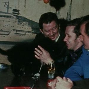 Miehet leikkivät koiran kanssa satamabaarissa Israelissa.