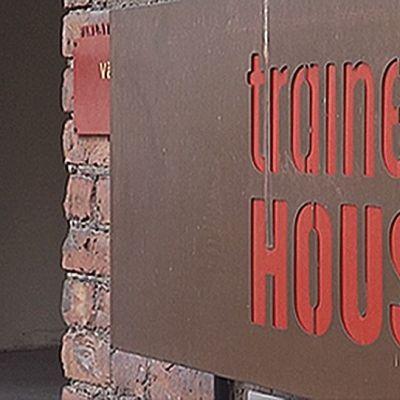 Trainers' Housen kyltti seinässä.