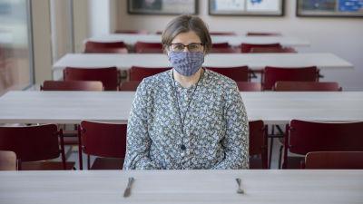 Kvinna med glasögon och munskydd sitter i en tom skolmatsal och ser mot kameran.