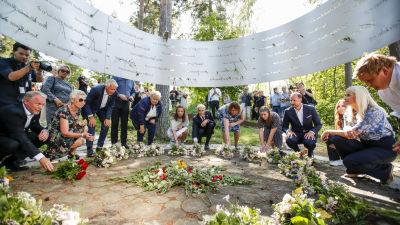Kungafamiljen och norska politiker sänker ner blommor vid minnesplatsen för offren i Utoya-massakern.