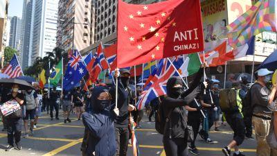 Bild på demonstranter som håller upp en banderoll med Kinas flagga där det står ''Anti-Kina''.