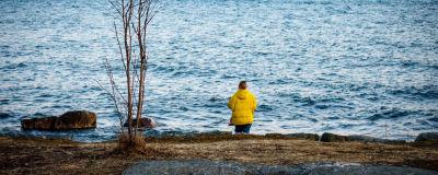 Nainen rannalla keltaisessa toppatakissa katselee kohti horisonttia.
