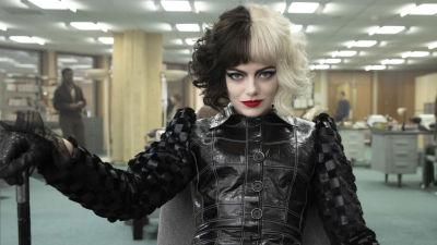 Närbild på Cruella (Emma Stone) som sitter och ser klurisk ut.