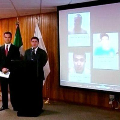 Poliisin edustajat  ja pidätettyjen heijastetut kuvat valkokankaalla.