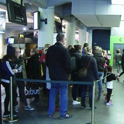 Ihmisiä elokuvateatterin kassajonossa.