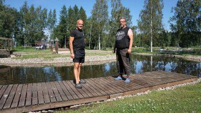 Två män står vid en damm. I bakgrunden syns en lekpark.