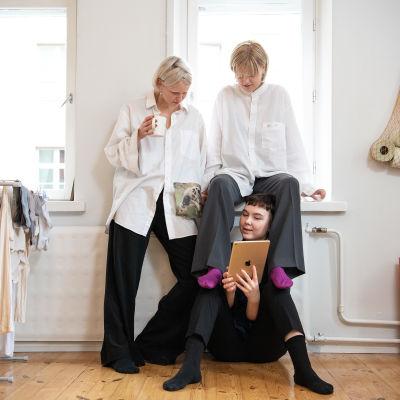 Kolme nuorta naista katselevat iPadia kimppakämpän olohuoneessa.
