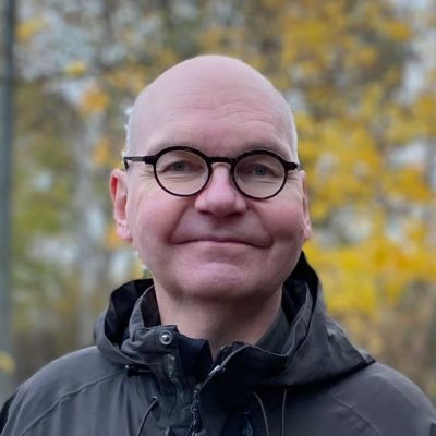 Heikki Kaukoranta på en väg med höstlöv i bakgrunden.