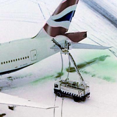 Mies ruiskuttaa nosturista vihreää jäänestoainetta lentokoneen päälle.