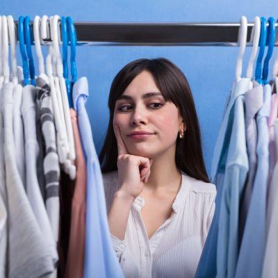 en vkinna står och tittar på kläder i en garderob