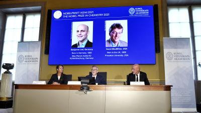 Bilder på nobelpristagarna i kemi Benjamin List och David MacMillan visas upp på en storskärm vid den kungliga vetenskapsakademien.