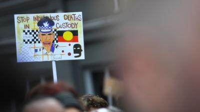 """Demonstranter i Sydney, Australien håller i en skylt med texten """"Stoppa ursprungsfolkens död i polishäkten"""" . Demonstranterna protesterar mot att så många aboriginer dött i polishäkte i Australien."""