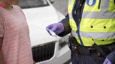Person i t-skjorta och en polis som har håller ett drogtest i handen.