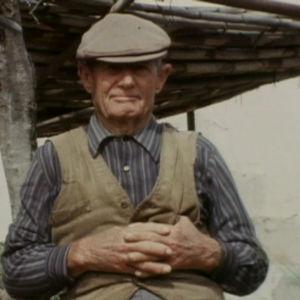 Los pacoslainen mies istuu kädet ristissä.
