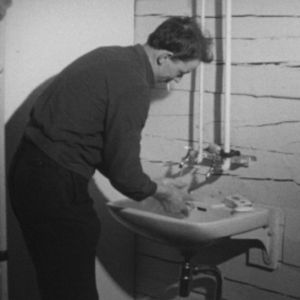Metsuri pesee käsiään savottamajassa vuonna 1964.