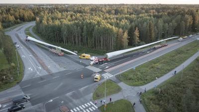 Flygfoto av två rotorblad som transporteras med lastbilar längsmed en landsväg i Karleby.
