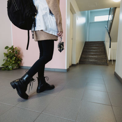 Kotihoidon hoitaja kävelee sisään kerrostalon rappukäytävään.