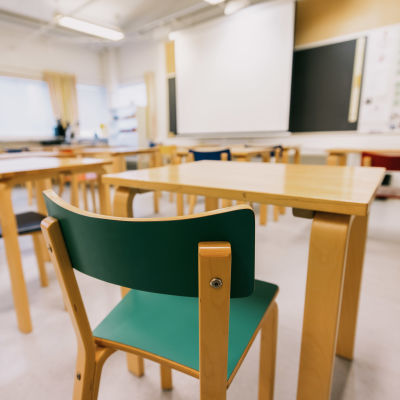 Ett tomt klassrum där stolar, pulpeter och en svart tavla syns.